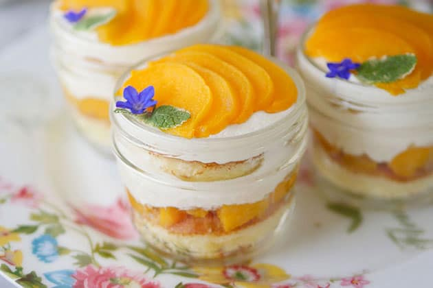 Peach cakes in a cup on the bottom level of an afternoon tea cake stand.