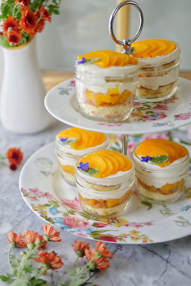5 peach cakes in a cup on a 2-tier afternoon tea cake stand.