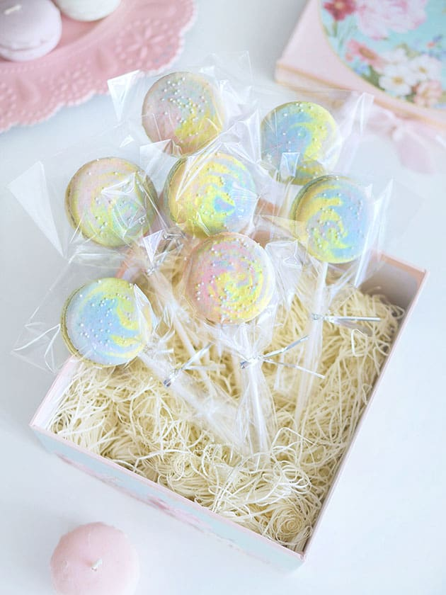 Multi-color galaxy macarons on a lollipop stick displayed in a gift box.