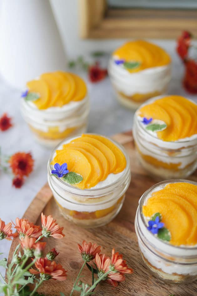 Peach dessert cups on a table counter with flowers.