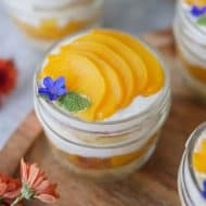 Slices of peach on top of cake in a jar.