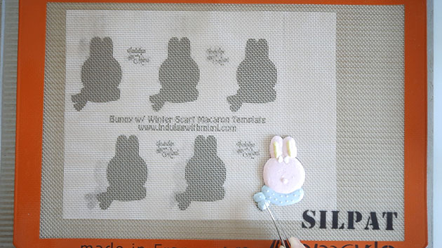 A bunny character macaron with multiple colors piped onto a silicone mat.
