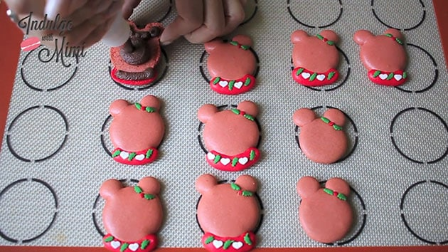 Chocolate peppermint ganache being piped onto Christmas bear macarons.