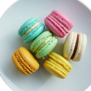 smooth round macarons in different colors on a plate.