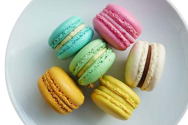 Round and smooth macarons in various colors on a grey plate.