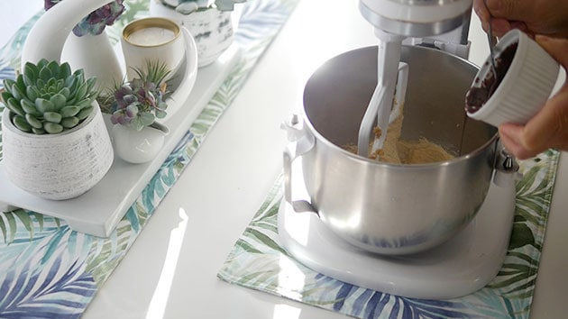 Hand pouring melted chocolate into a mixer with pound cake batter.