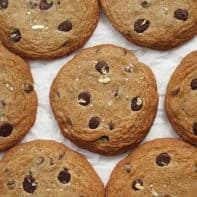 Large chocolate chip cookies with gold flakes laid out in a row on parchment paper.