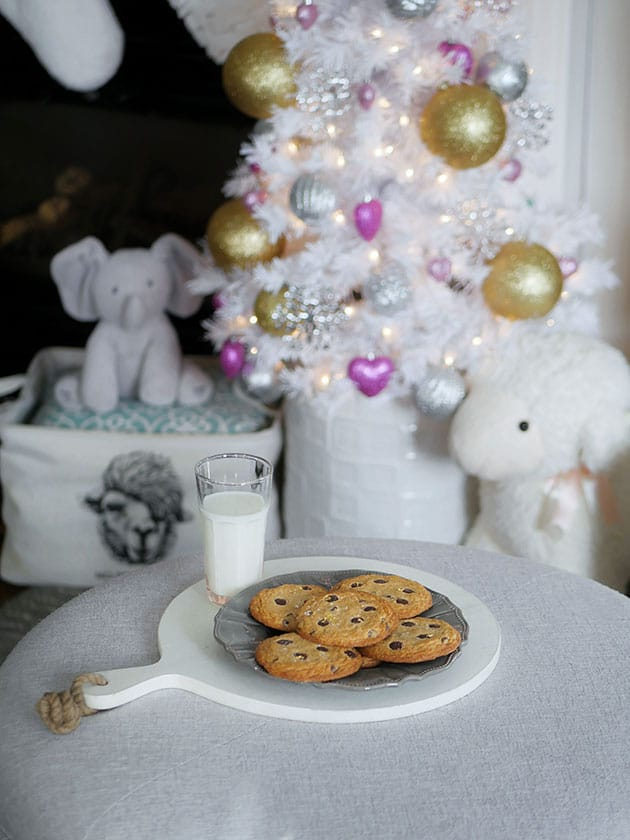 Cookies on a plate with milk for Santa in front of a Christmas tree.