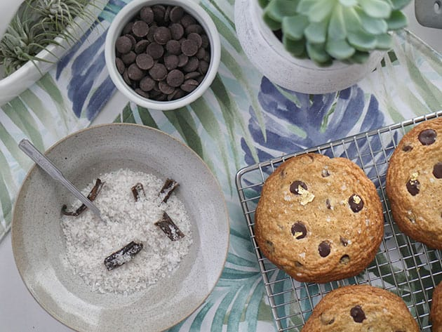 Maldon vanilla salt with chocolate chips next to cookies cooling on a rack.