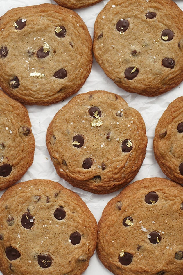 Fancy chocolate chip cookies with edible gold flakes laid out on parchment paper.
