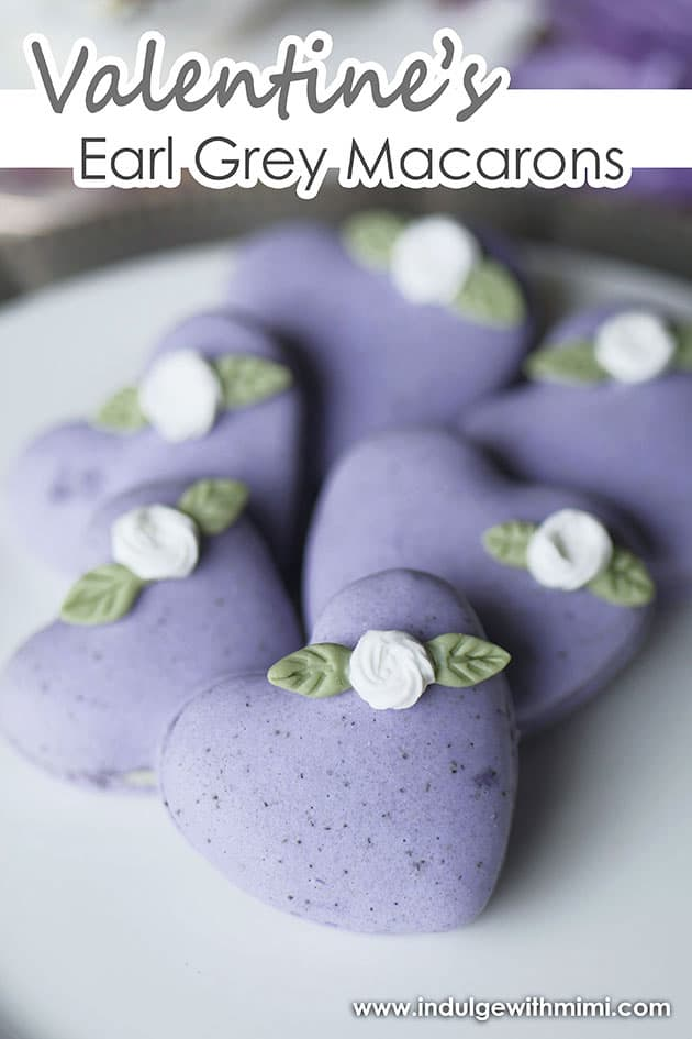 |Purple earl grey macarons in a heart shape laid out in a staggard pattern.