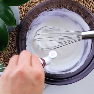 Hand adding food color into meringue.