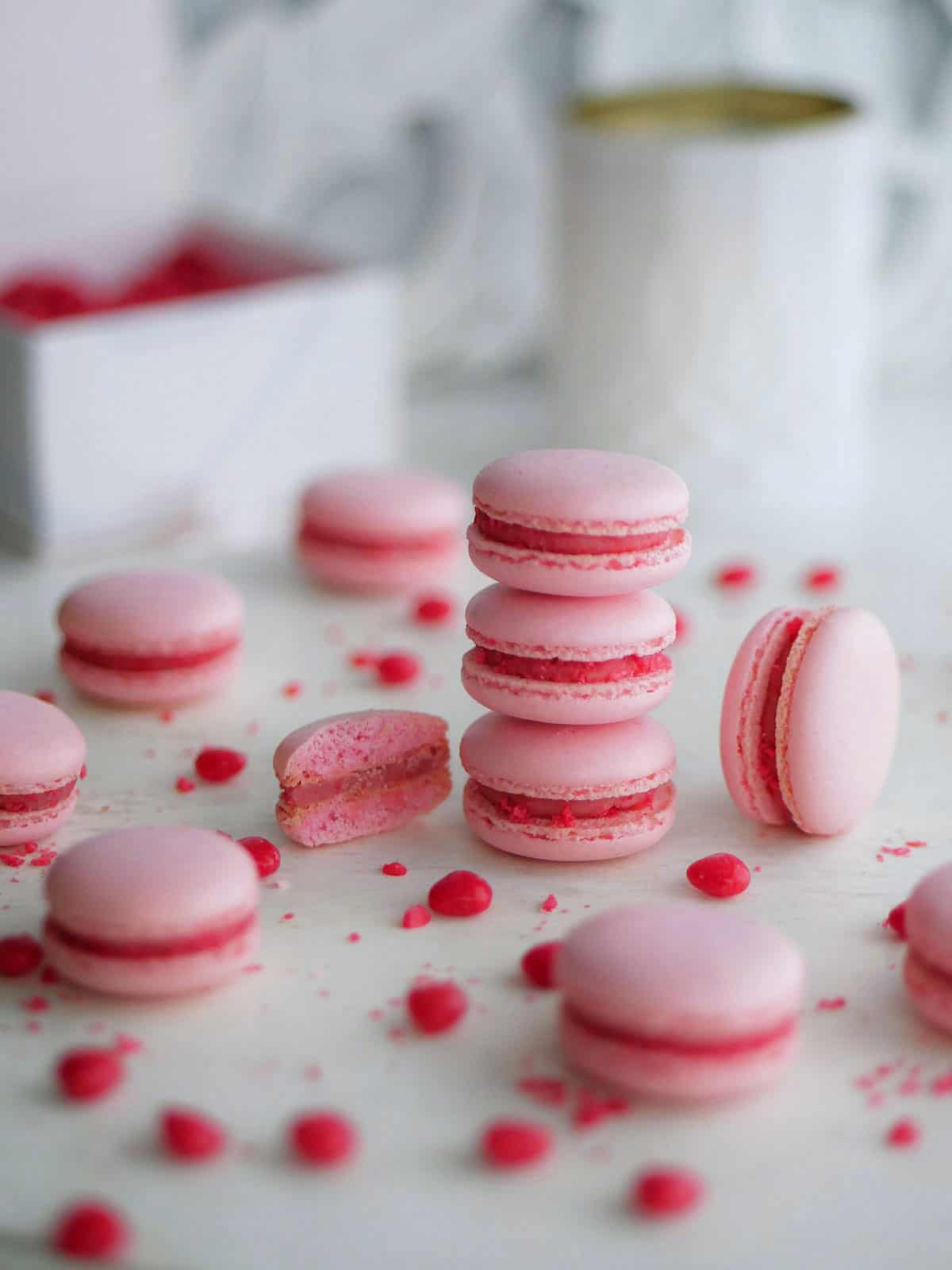 A whole tabletop filled with pink macarons with non-hollow one cut open.