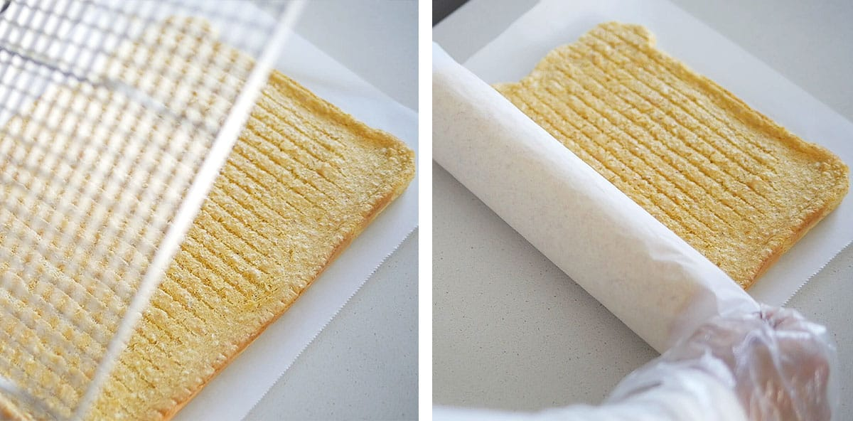 The flat layer of cake being rolled into a roll with parchment paper.