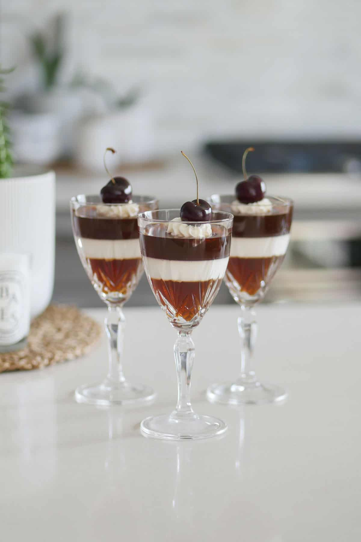 Three coffee jelly desserts in crystal stemware on a white quartz countertop.