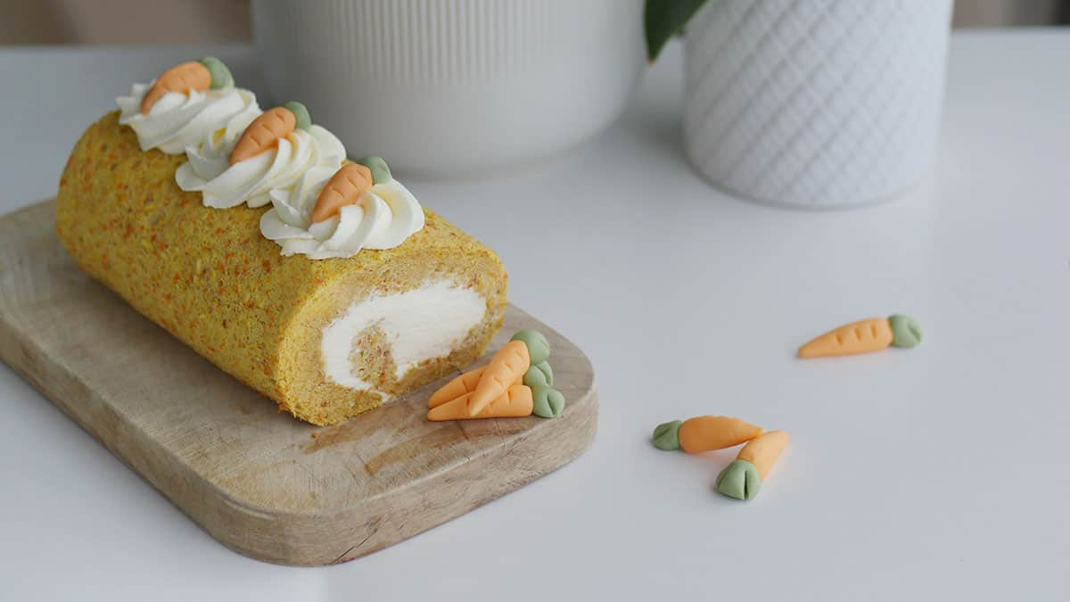 Carrot cake roll on a wooden cutting board with some fondant carrots and mascarpone cream piped on the top.