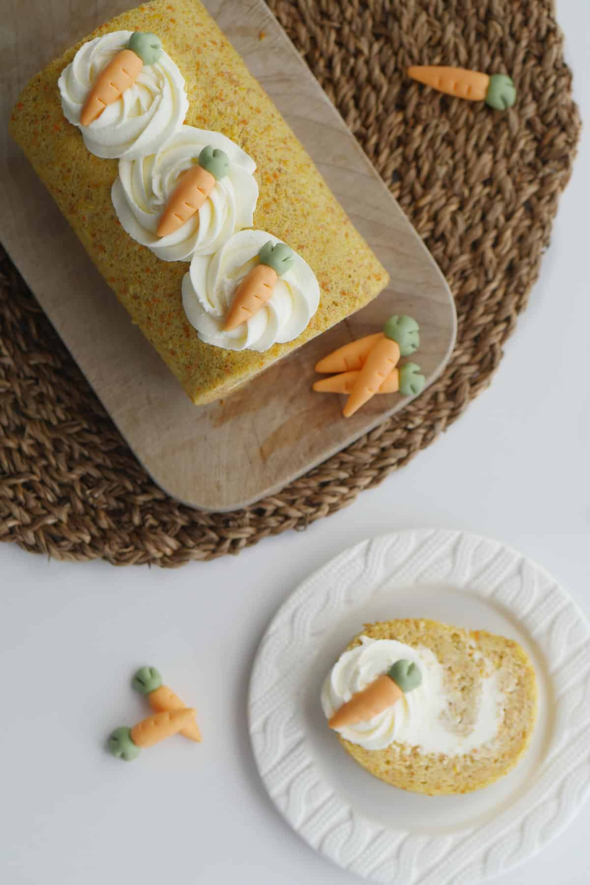 Top view of fully assembled carrot cake with a slice cut out and placed on a small plate.